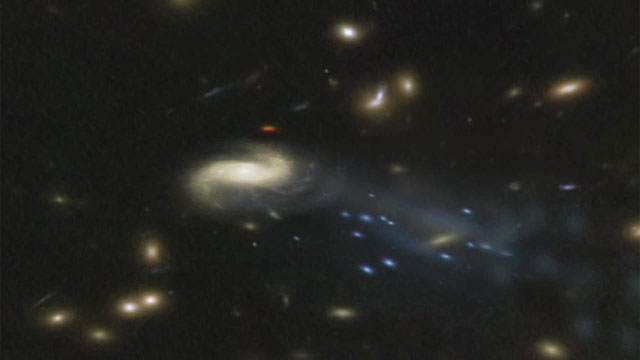 "Hubble sees ""Comet Galaxy"" being ripped apart by galaxy cluster"