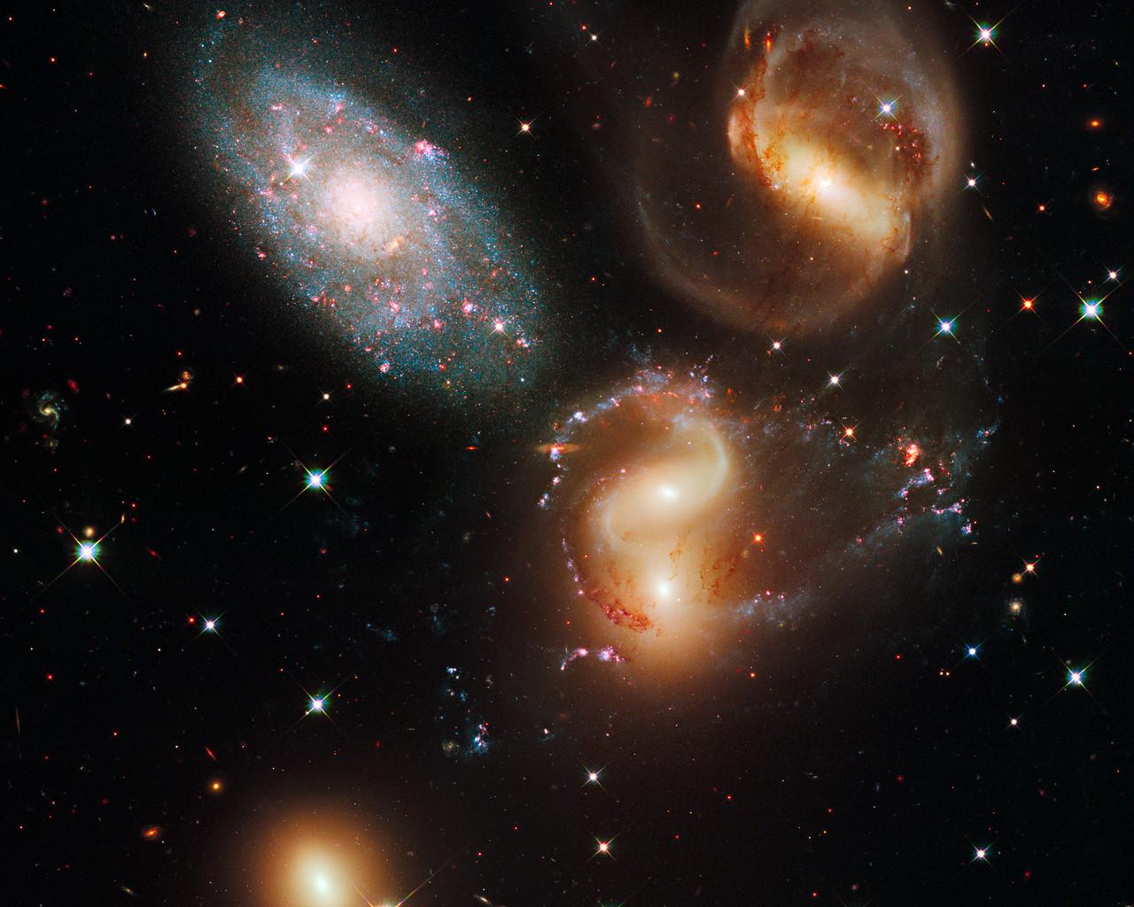 Настоящий космический джек-пот: пять галактик на одном снимке в такой близости друг от друга! Обнаружил их французский астроном Жан-Мери Стефан, аж в 1877 году. В честь него группа галактик получила имя — квинтет Стефана. Четыре галактики находятся в постоянном взаимодействии, а большая зелёная дуга в правой части снимка — ударная волна от столкновения двух из них (тех, что находятся в центре)